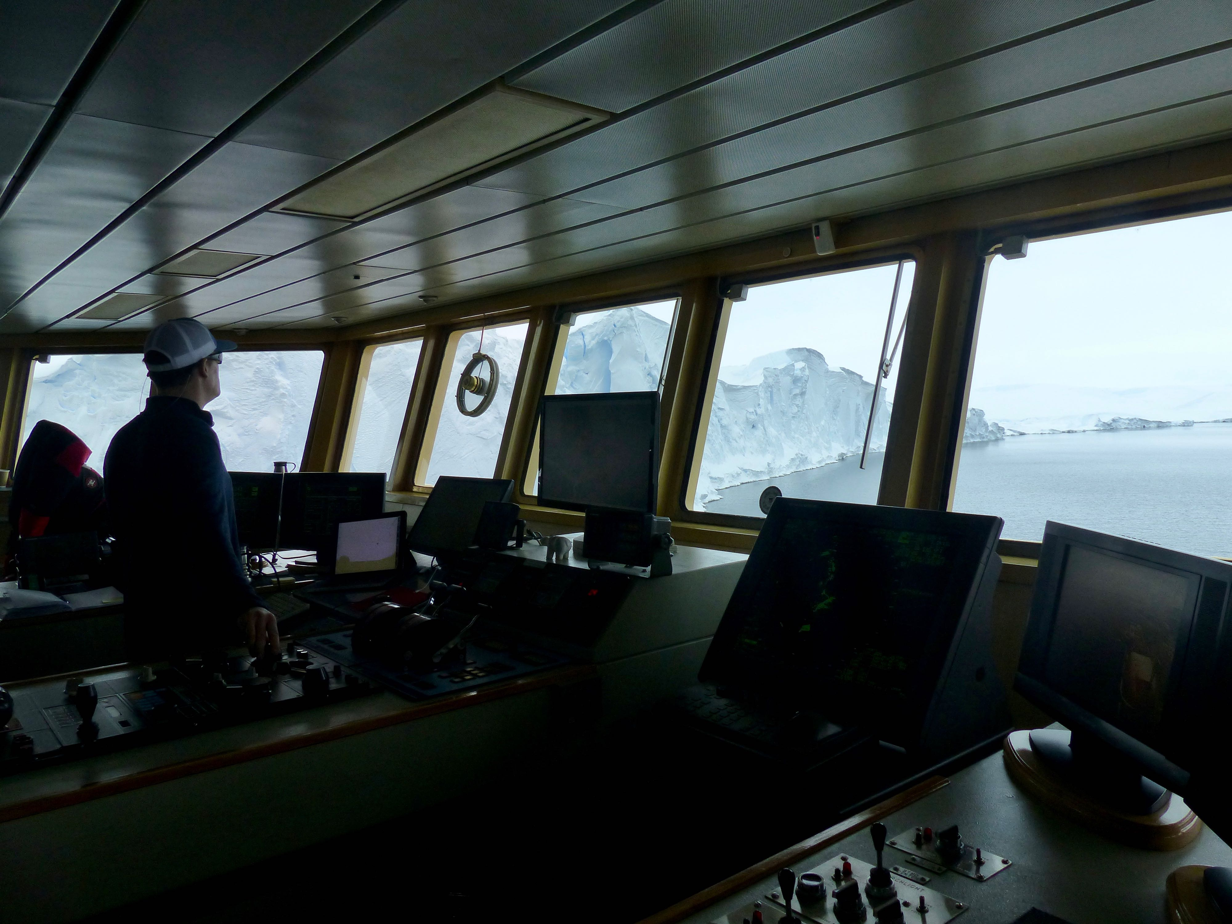On the bridge of the ship, Luke Zeller, the third mate onboard the Palmer, navigates the ship a few hundred meters from the Thwaites ice front. As directed by the THOR's multibeam experts, he manuevers the ship so that the multibeam can map along the entire Thwaites ice front and as much as a kilometer underneath. Photo credit: Tasha Snow