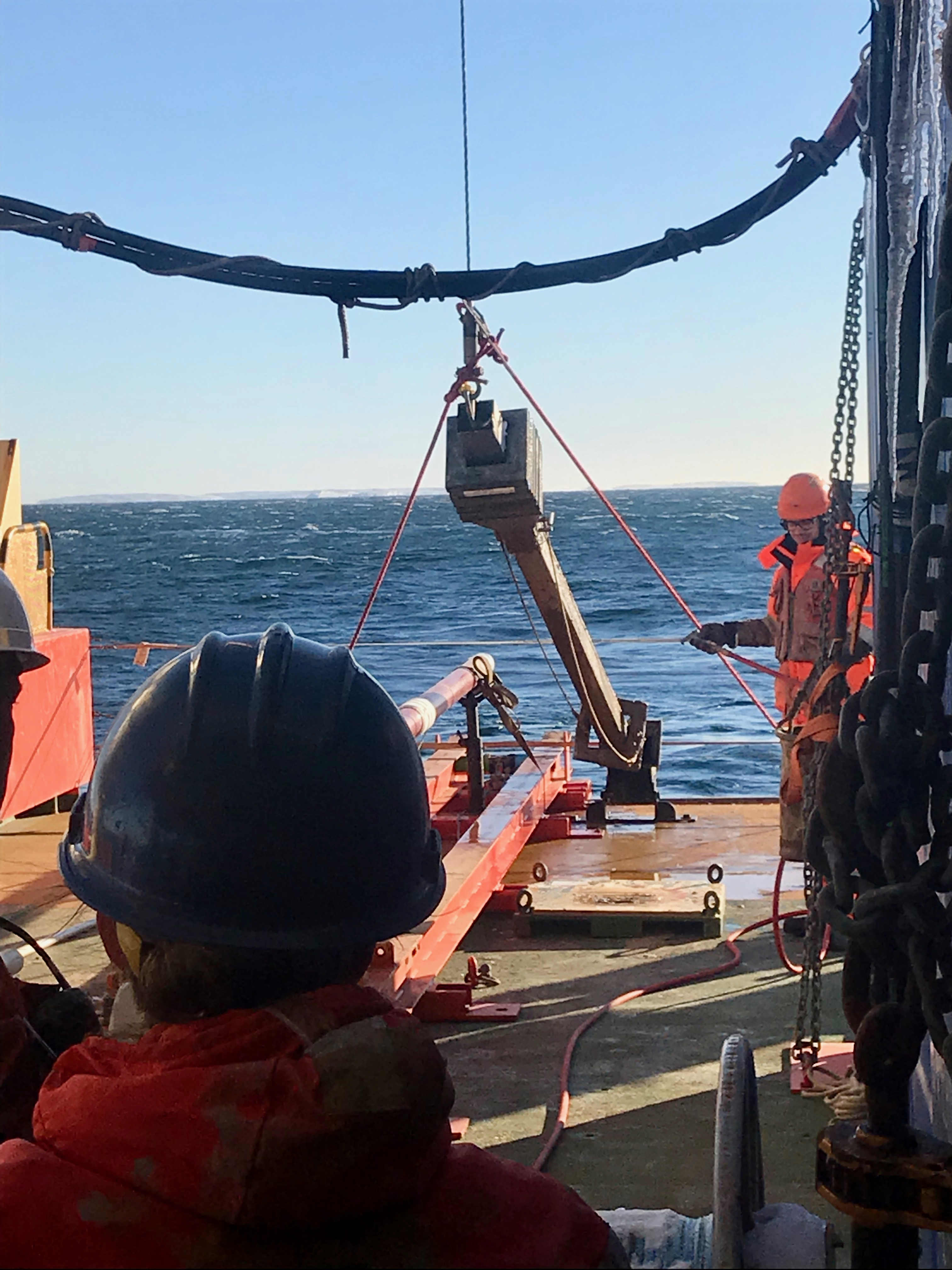 Peter Sheehan helps to secure and hose off the Kasten core just brought back up from the seafloor. Becky Minzoni waits excitedly for the core to be secured on the ship so that her team can open up the core to see if they successfully captured a sediment core.