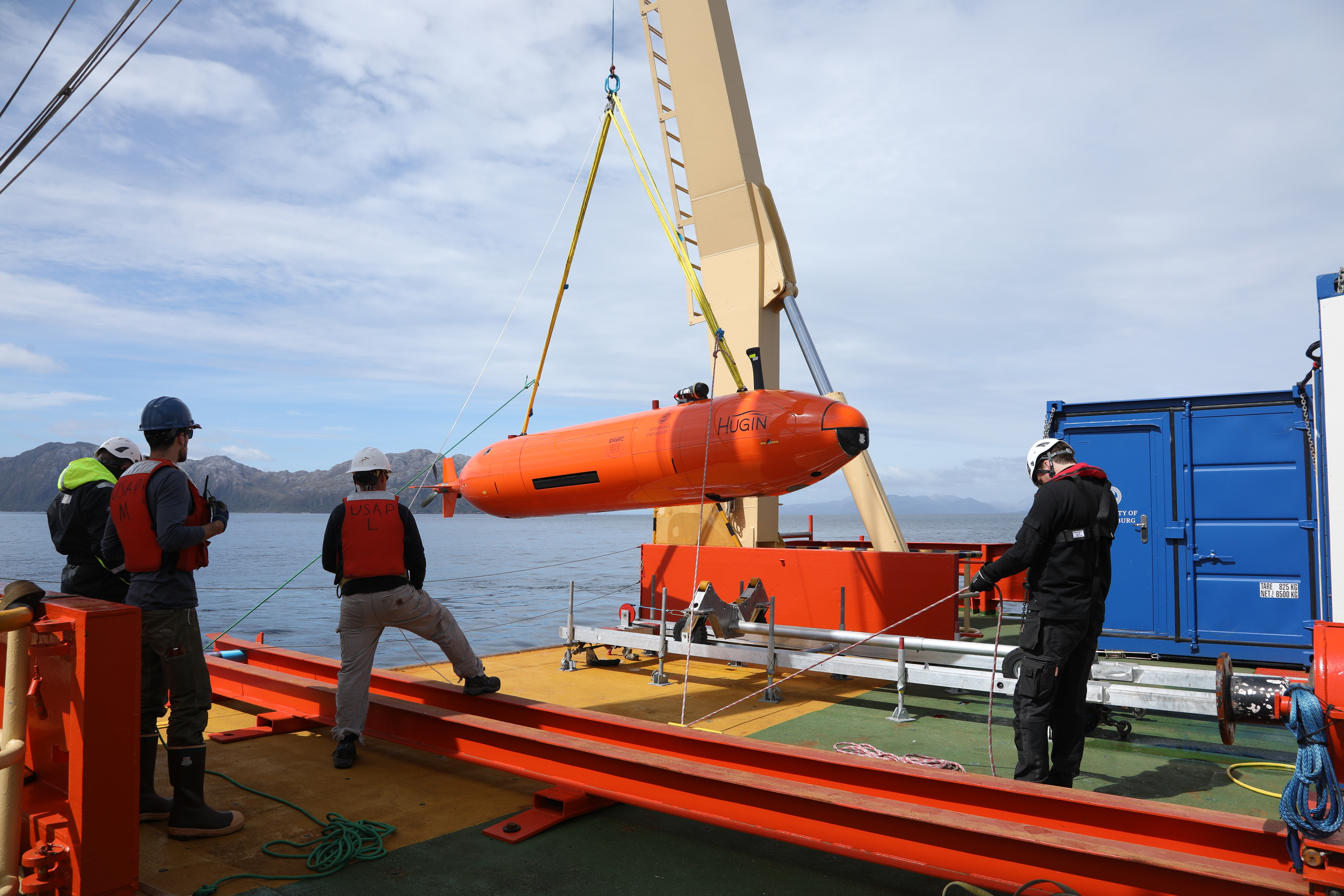 Crew members guide the Hugin as the A-frame lifts it off of the deck and into the water. (credit: Linda Welzenbach).