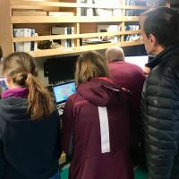 Scientists gather around computers to learn the latest discoveries about the Thwaites Glacier ice shelf.