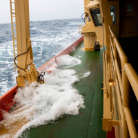 Huge waves crash up onto the deck of the Nathaniel B. Palmer as it crosses the Drake Passage. Credit: Carolyn Beeler/The World